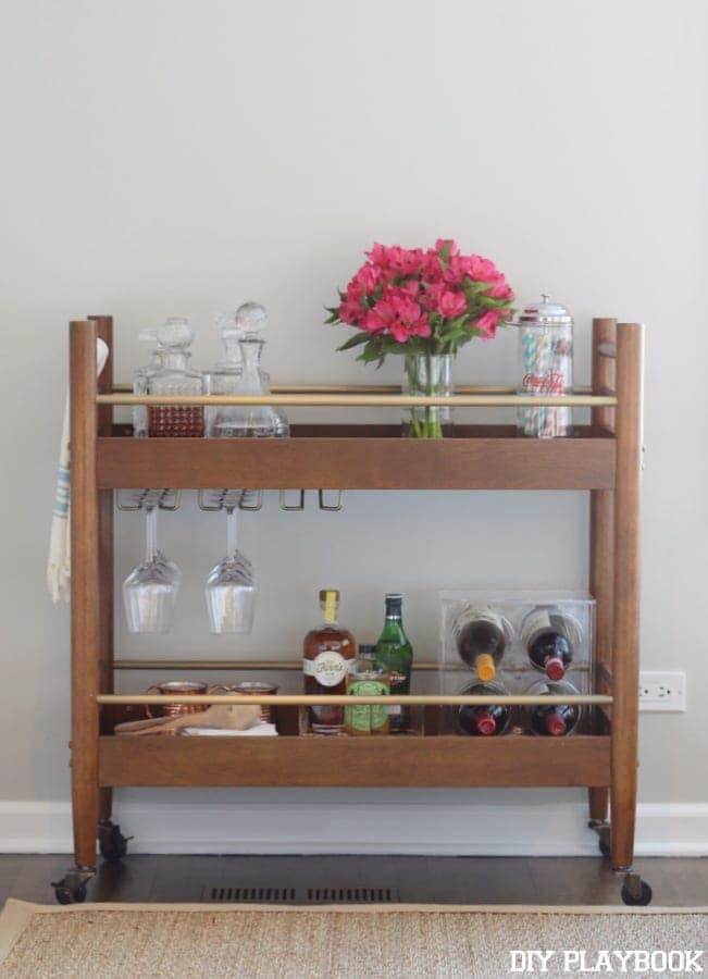 This decorated bar cart adds character to the living room space.