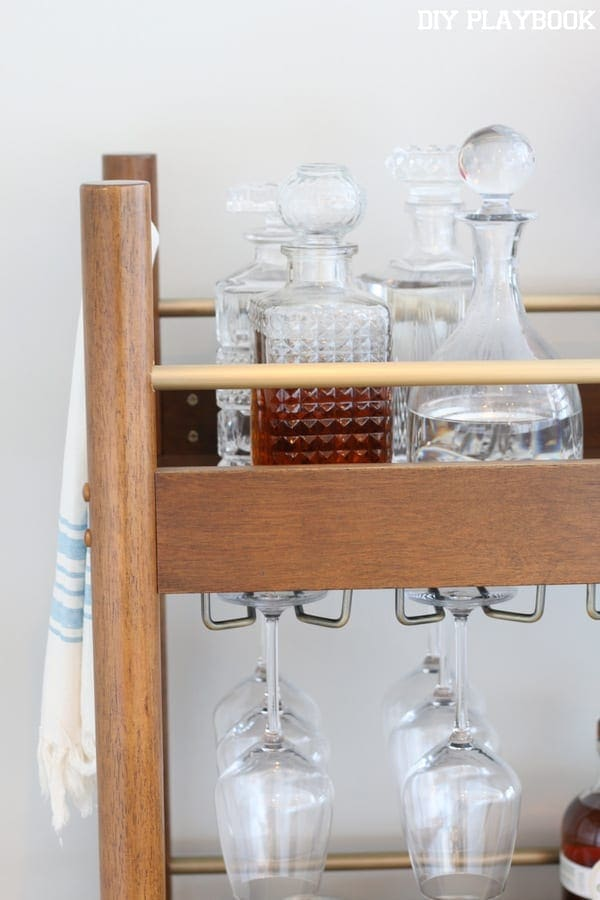 These glass decanters on the bar cart add elegance.