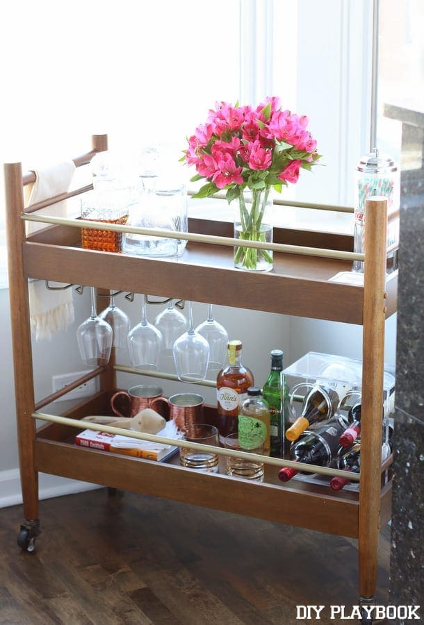 This elegant bar cart features fancy glassware and fresh pink flowers.