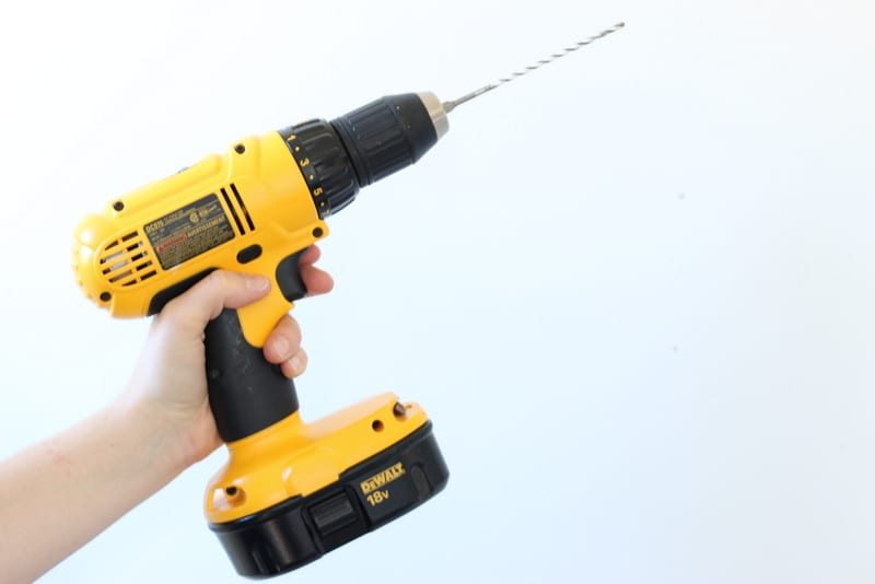 Using a DeWalt drill to hang shelving.
