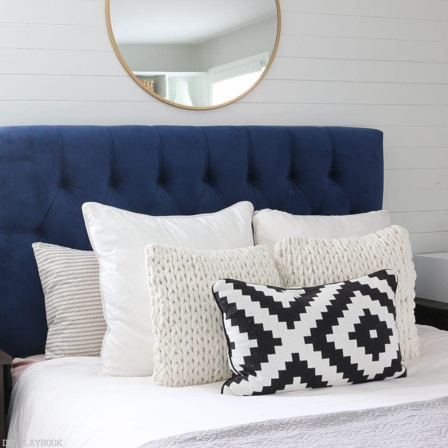 the master bedroom bed decor focuses on navy blue and white