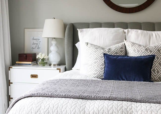 The pop of blue in the accent pillow pairs well with the white and gray tones of the room.