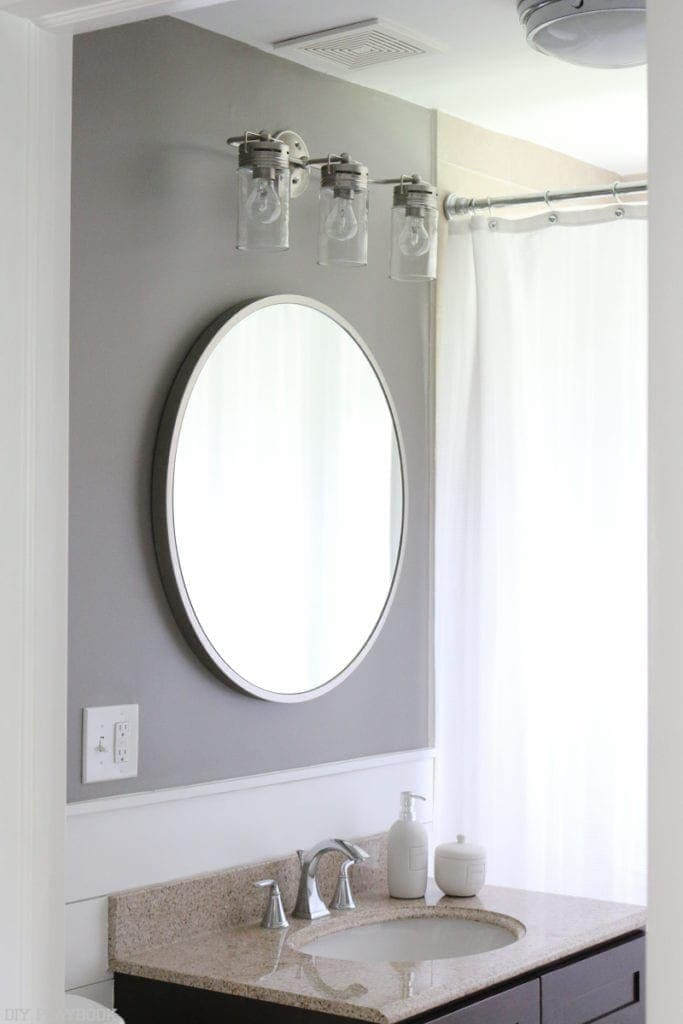 Bathroom with grey accent wall above the vanity and silver accents on the fixtures.