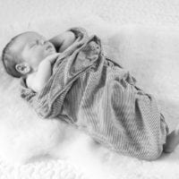 Babies are more comfortable being swaddled even in photos.