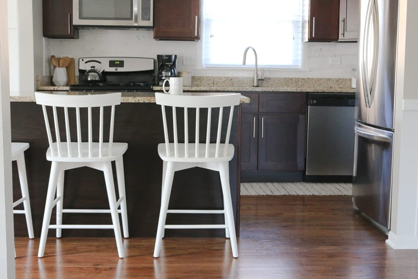 Time to see the kitchen! Love how those white stools contrast with the dark kitchen cabinets.
