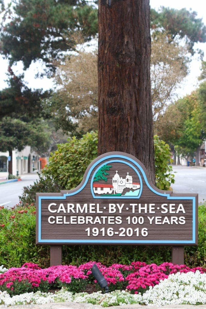 Town sign for Carmel-by-the-Sea, celebrating 100 years.