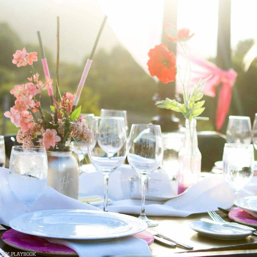 Beautiful tablescape with poppies and bright flowers next to white dishes.