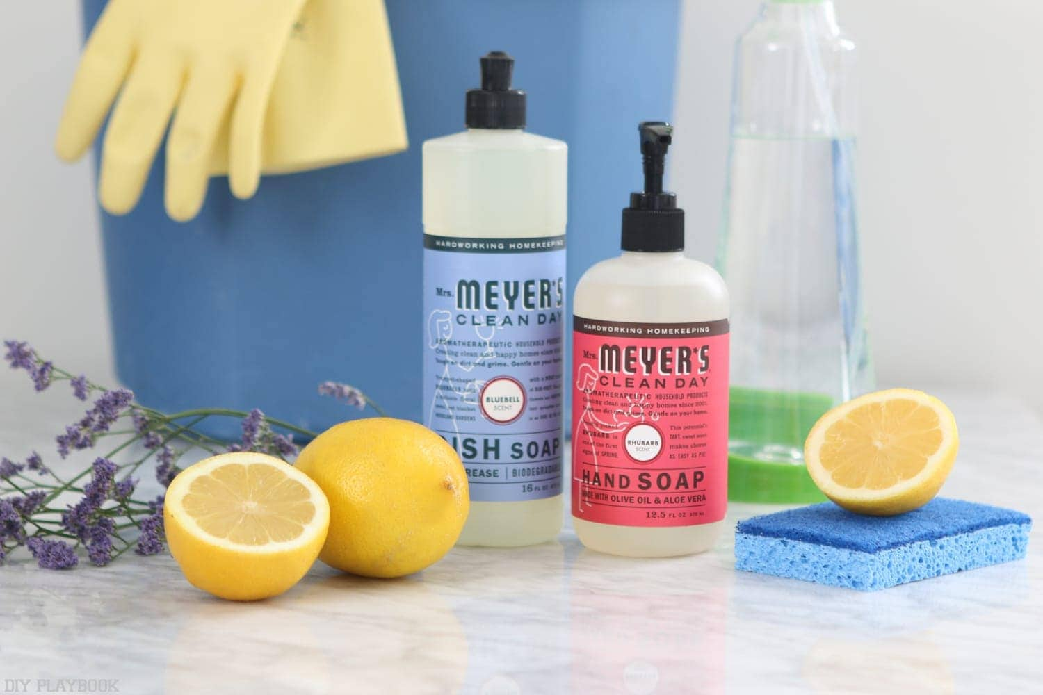 Cleaning essentials; lavender and lemon, dish soap, hand soap, dish sponge and a cleaning bucket with dish gloves.