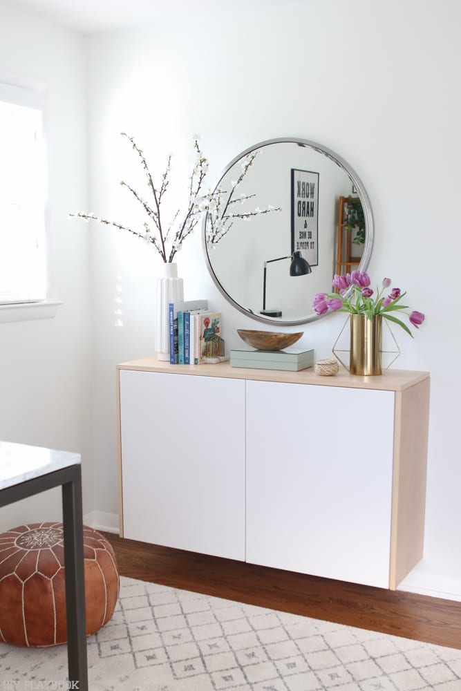 Floating cabinet and mirror in an office space with neutral colors.