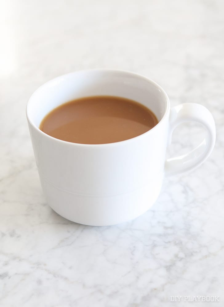 A plain white mug with coffee and creamer.