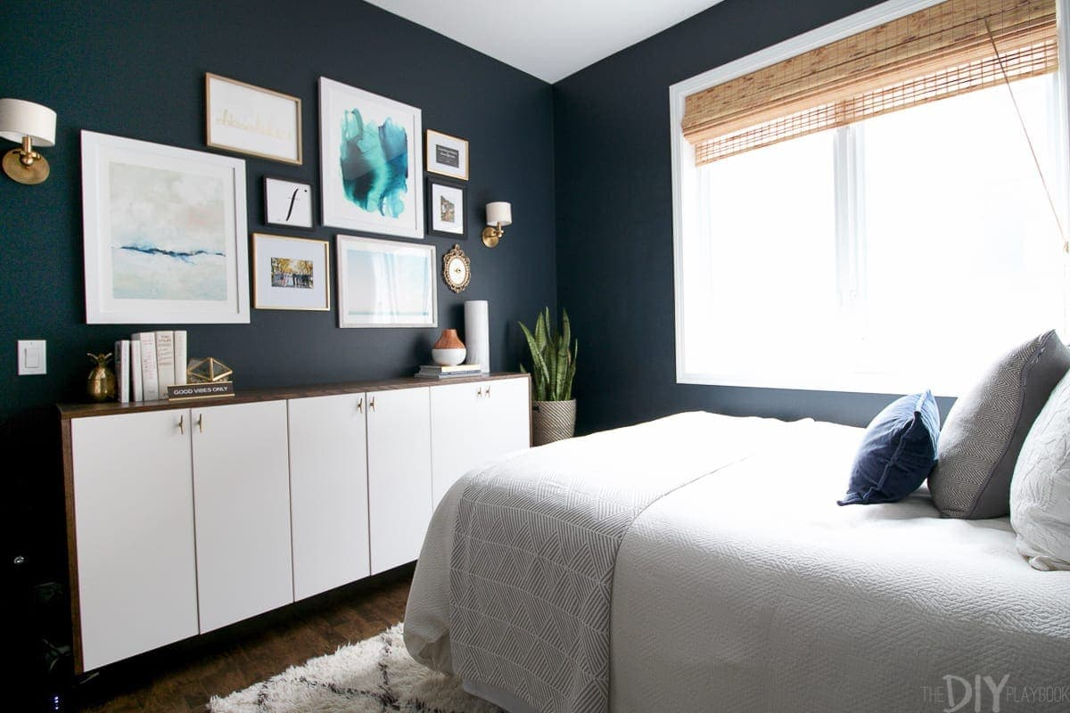 The guest bedroom has undergone a lot of changes, including navy paint on the walls! And we added a faux-denza, a gallery wall and wall sconces.