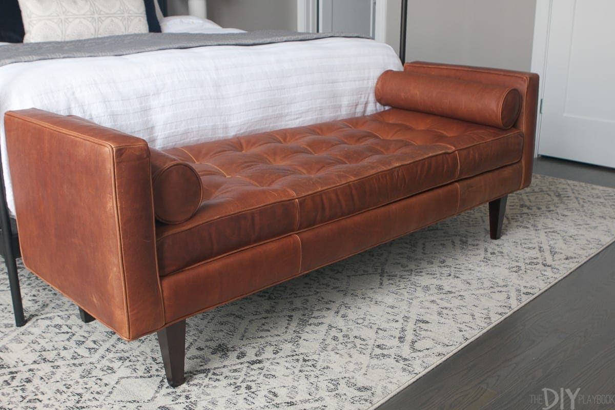 Stylish and modern brown leather bench at the foot of the master bed.