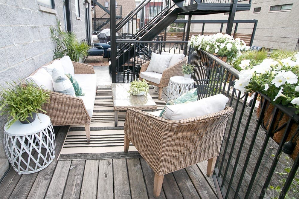 Our small outdoor patio got a major makeover with the addition of new wicker furniture, a rug and coffee table and lots of planters!