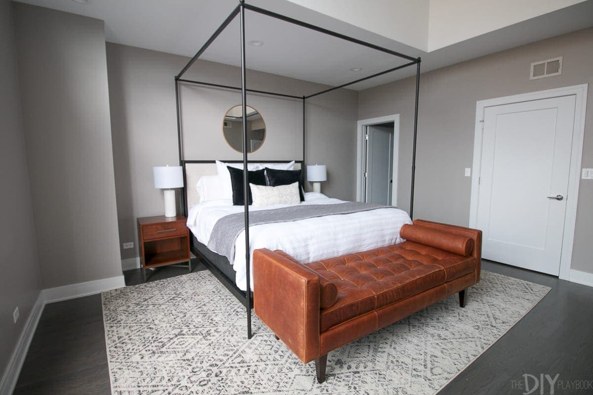 This modern master bedroom design looks so sleek and sophisticated with the gray and black color scheme. The pops of brown from the bench and nightstands give the room a warm touch.