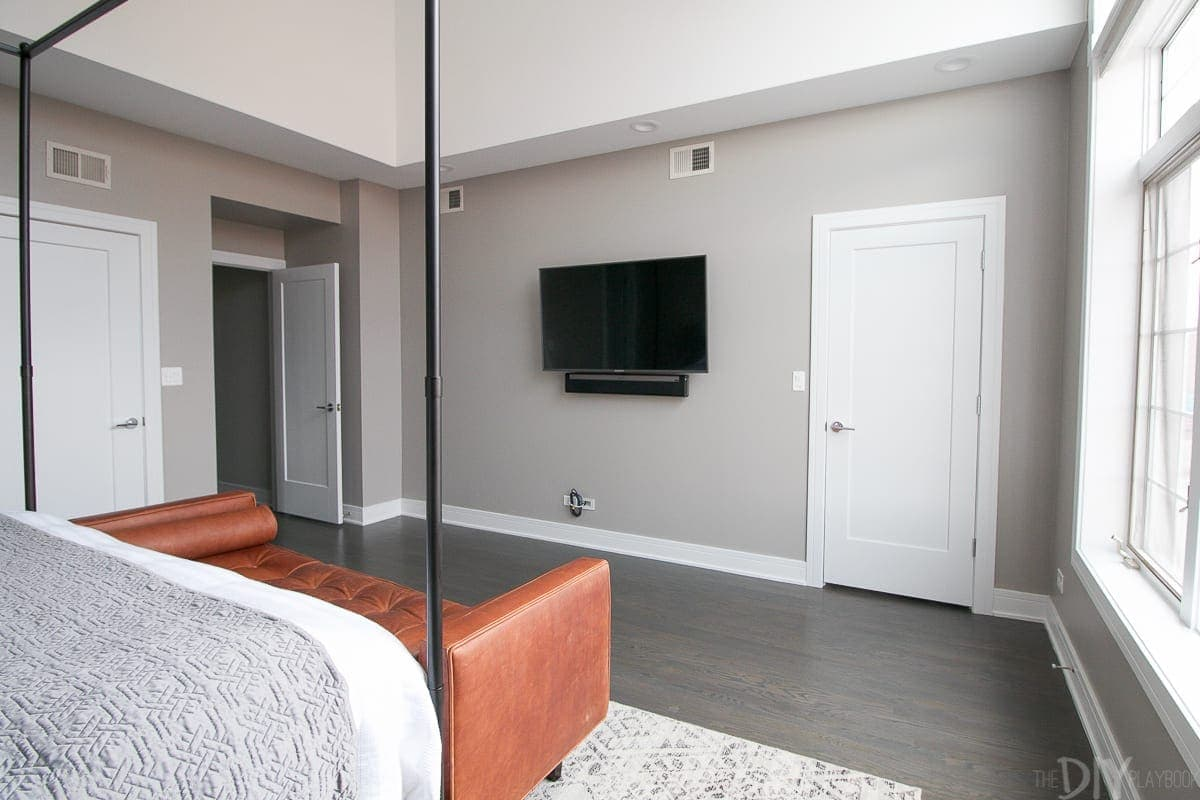 Wall opposite the bed with a mounted TV and the master bedroom entryway and bathroom door.