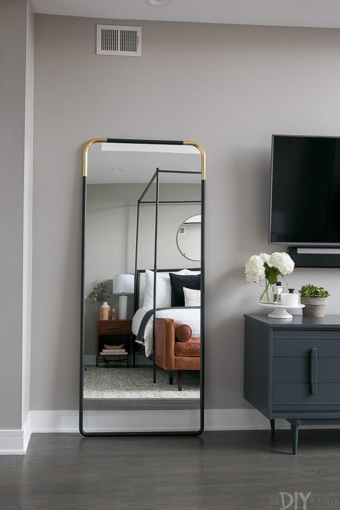 A master bedroom with a black and gold full-length mirror.