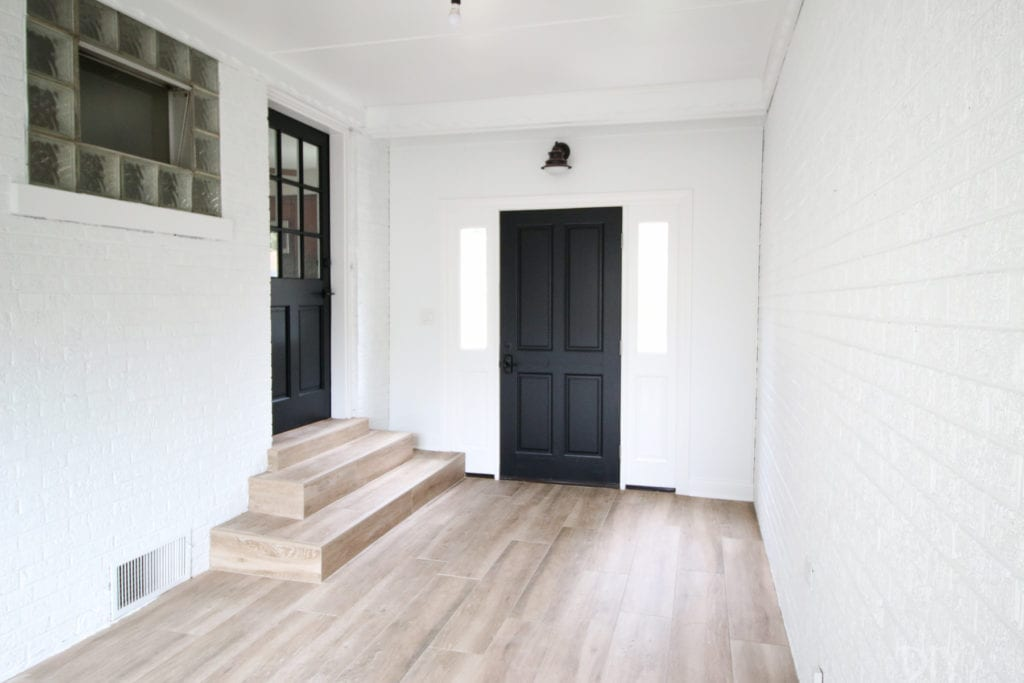 A white and black mudroom with faux wood tile