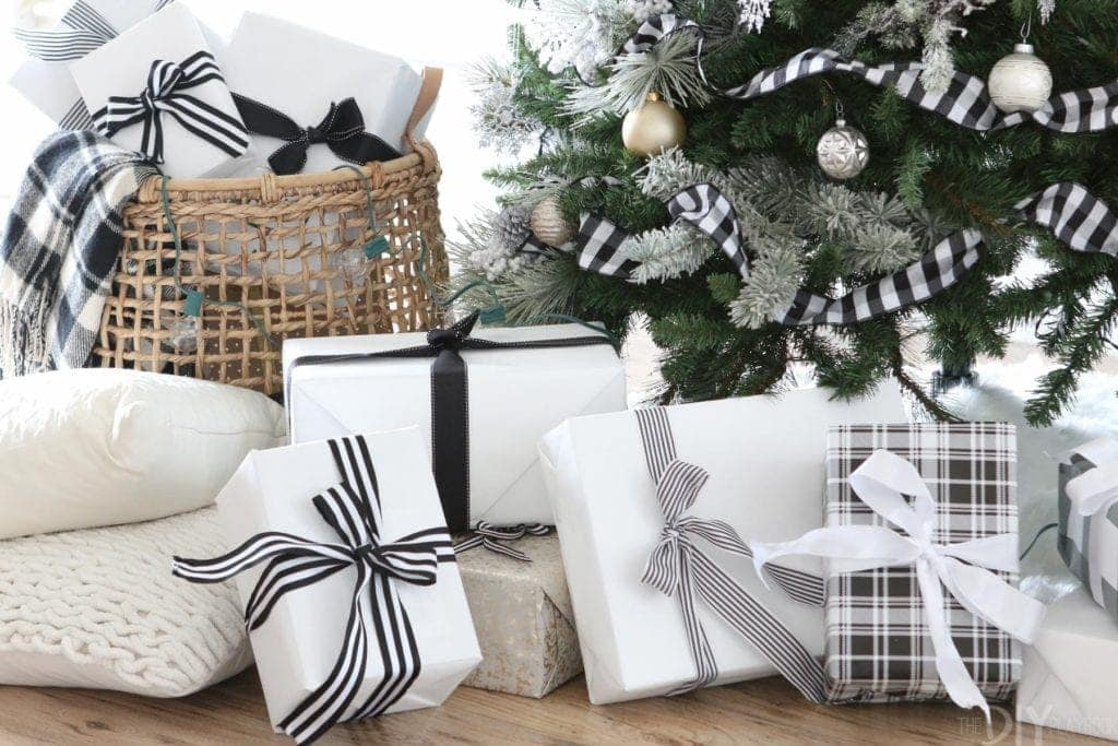 White and black gifts wrapped under a tree