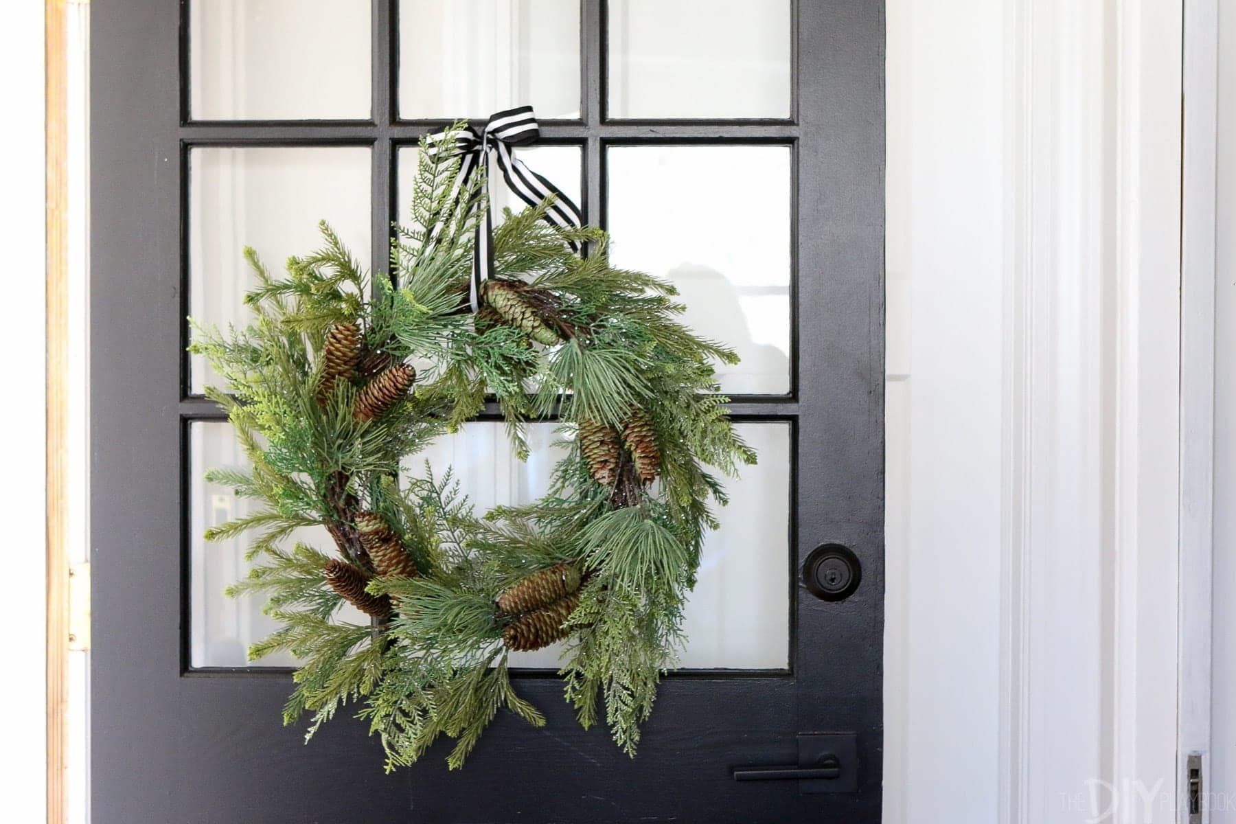This black windowpane door is really dressed up for the holidays with a simple pine bough wreath.