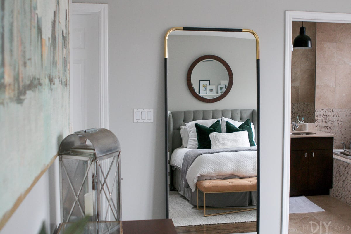 CB2 gold and black full-length mirror in the bedroom.
