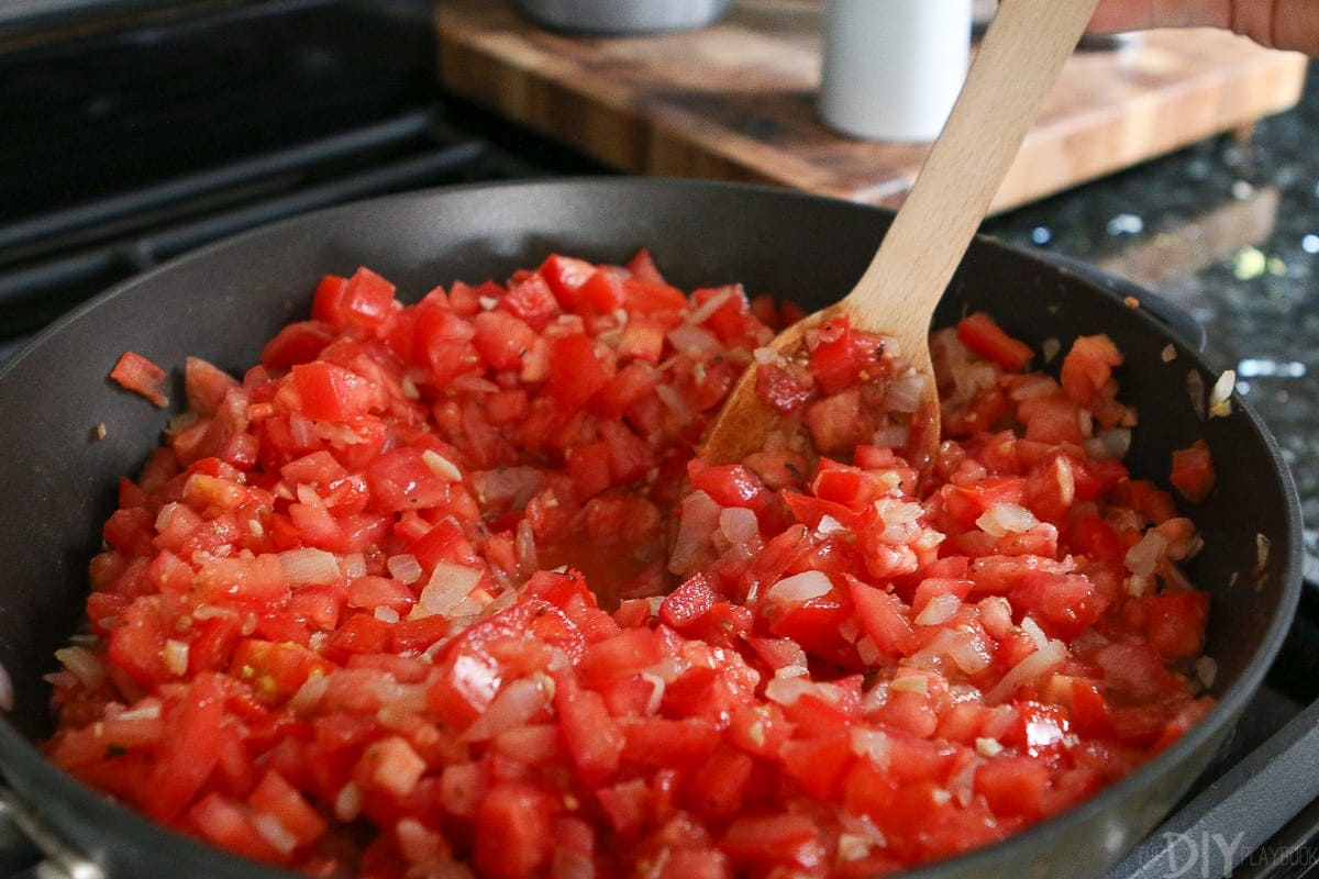 Adding chopped tomatoes to the onion and garlic mixture in a large skillet.