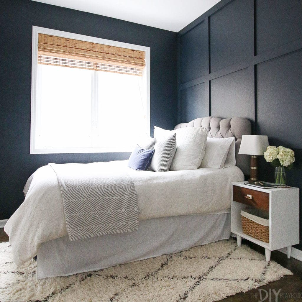 A navy guest room with white bedding