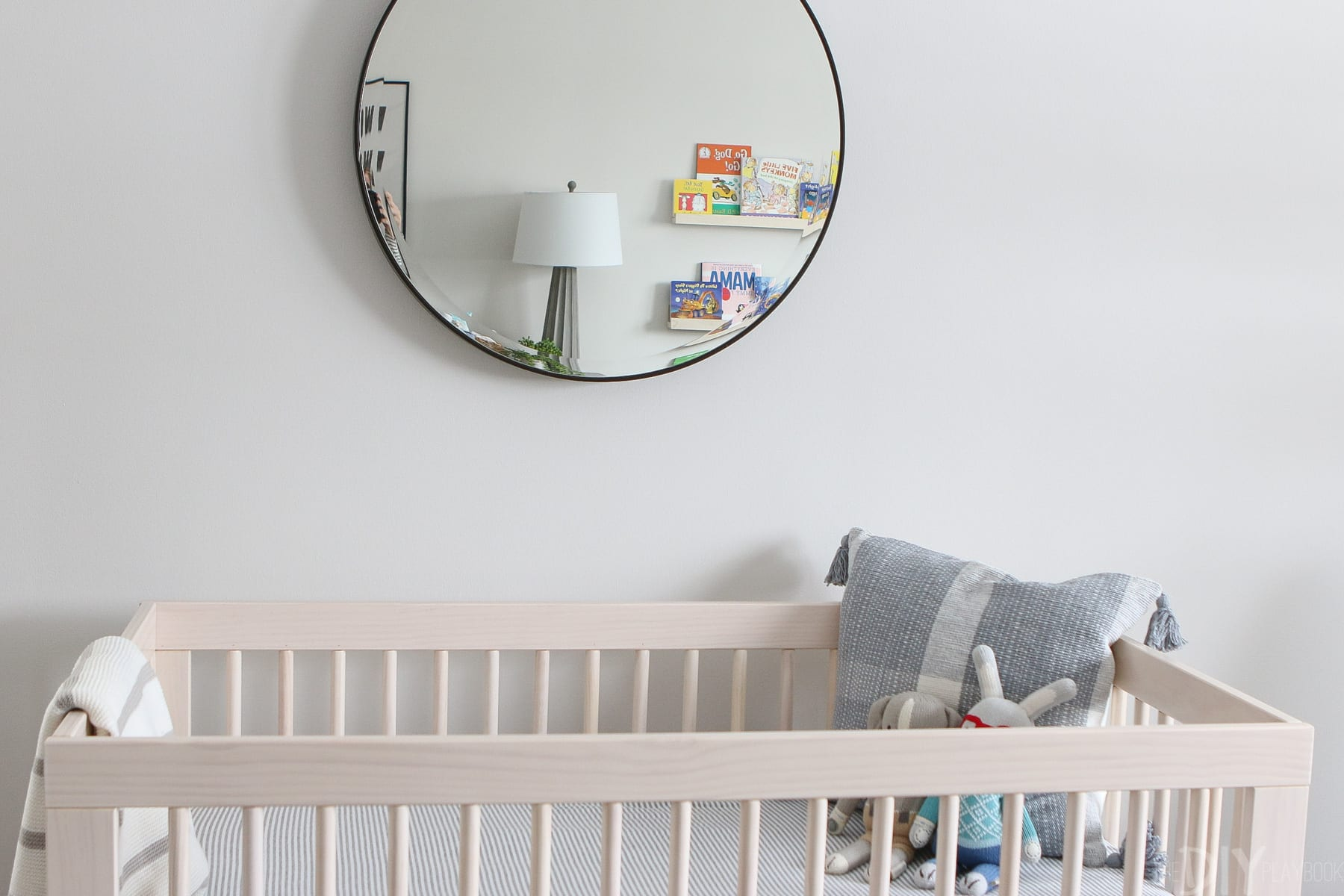 Round mirror over a natural wood crib