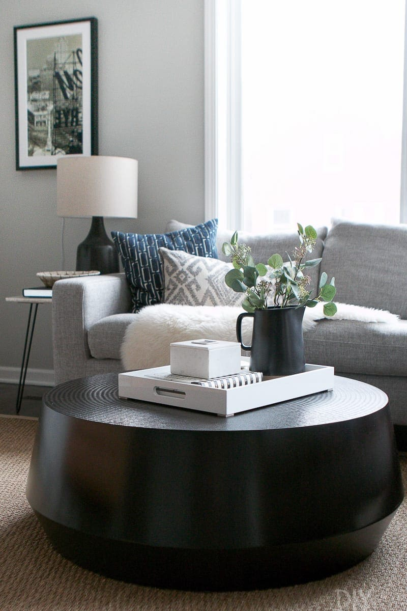 A black round coffee table complements the straight lines of a gray sectional in this family room.