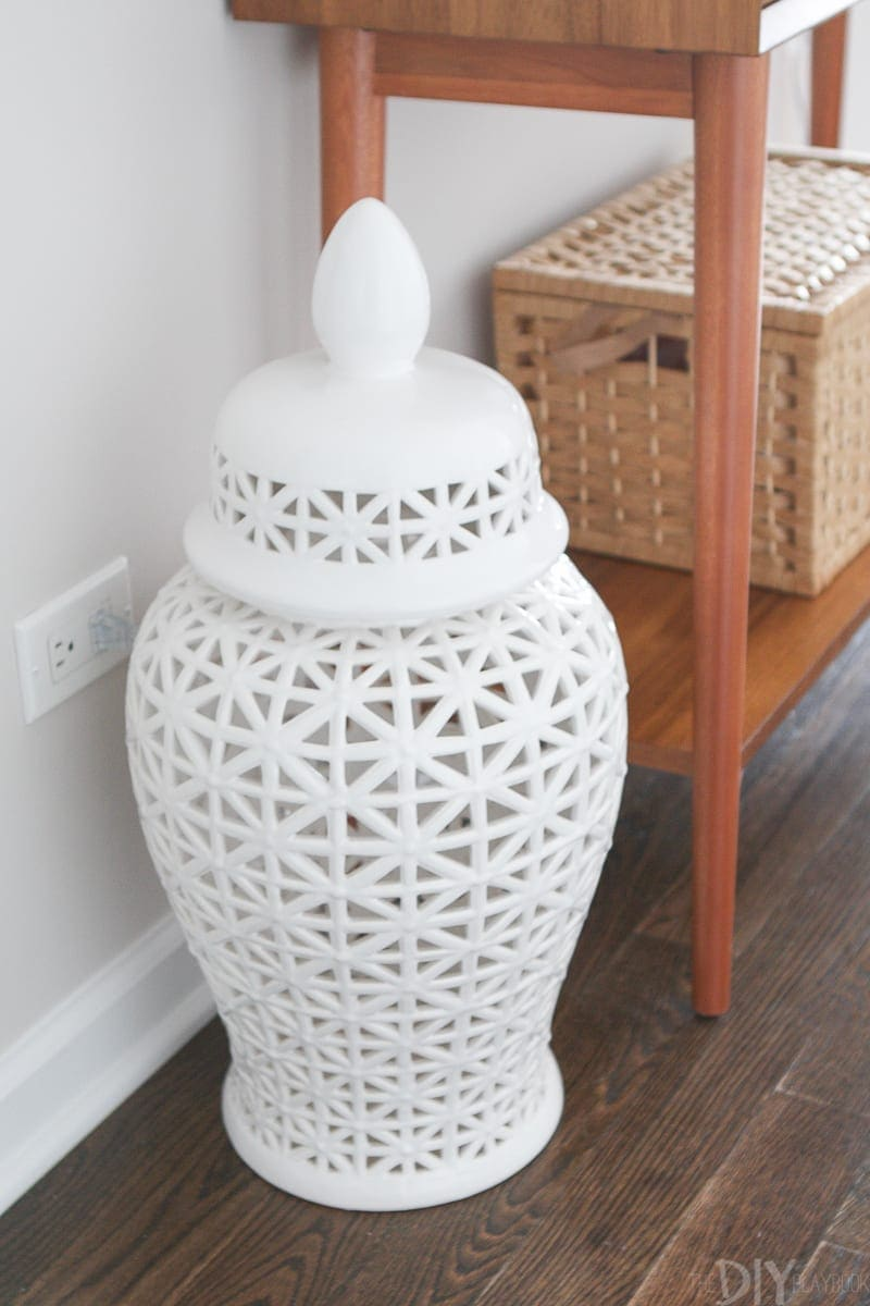 This large white vase covers an outlet in this functional entryway