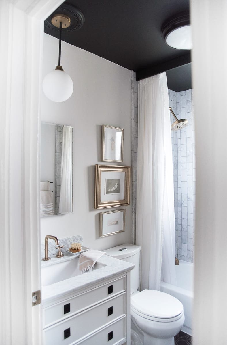 A white, black, and marble bathroom from the blog Room for Tuesday.