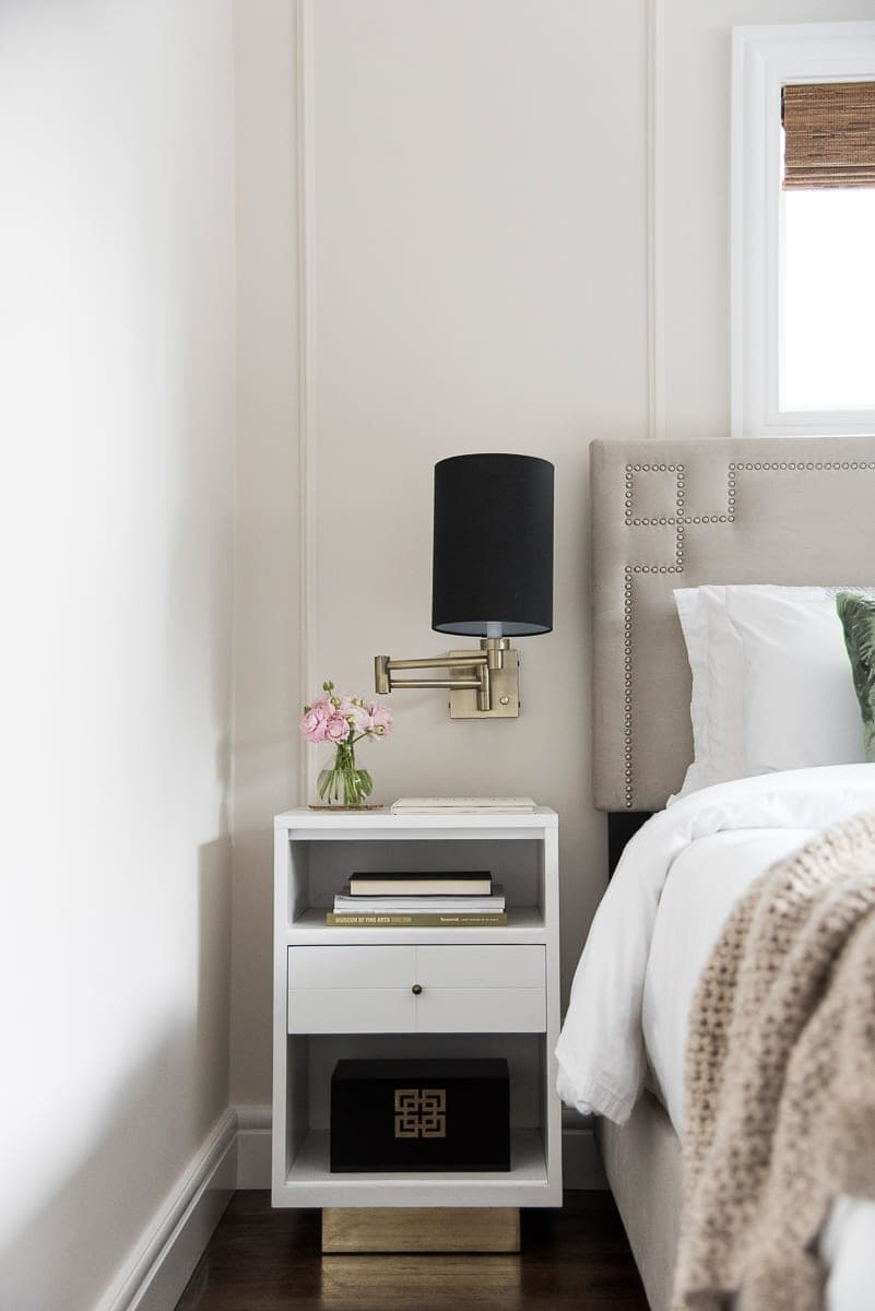 A white nightstand with gold and black sconces.