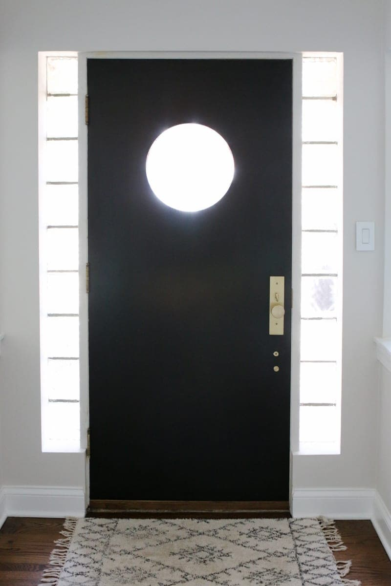 A black front door with satin brass hardware makes a statement in this bright home