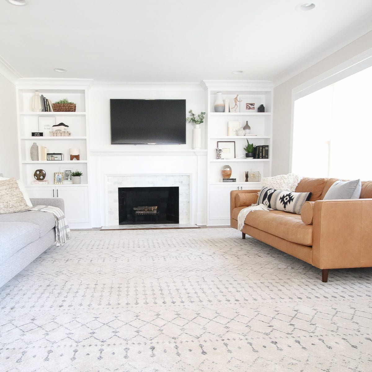 This white and gray area rug complements the leather sofa in a living room.