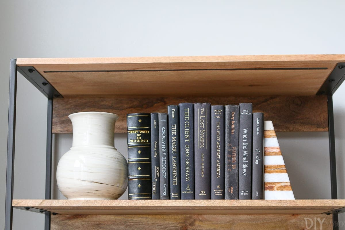 I love to sandwich hardcovered books with pretty vases and sculptural objects on a shelf.