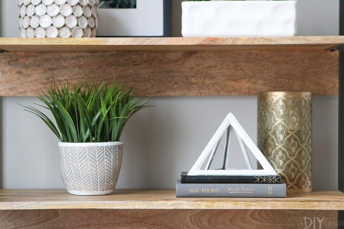 Faux greenery adds life to a bookshelf.