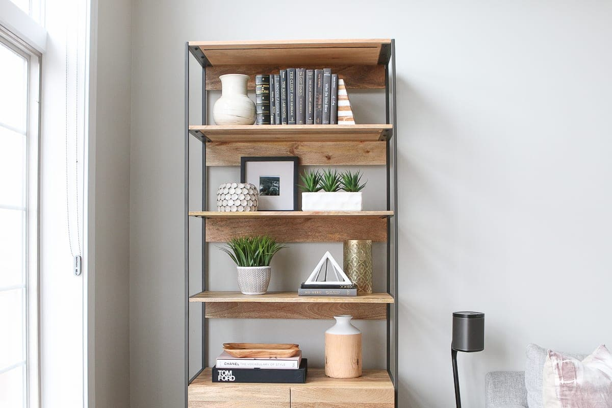 Tips to style bookshelves. Fill them with books, accessories, and greenery for a styled look.