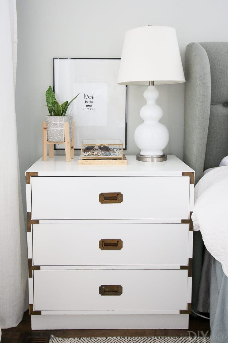 A white campaign style nightstand decorated in this master bedroom.