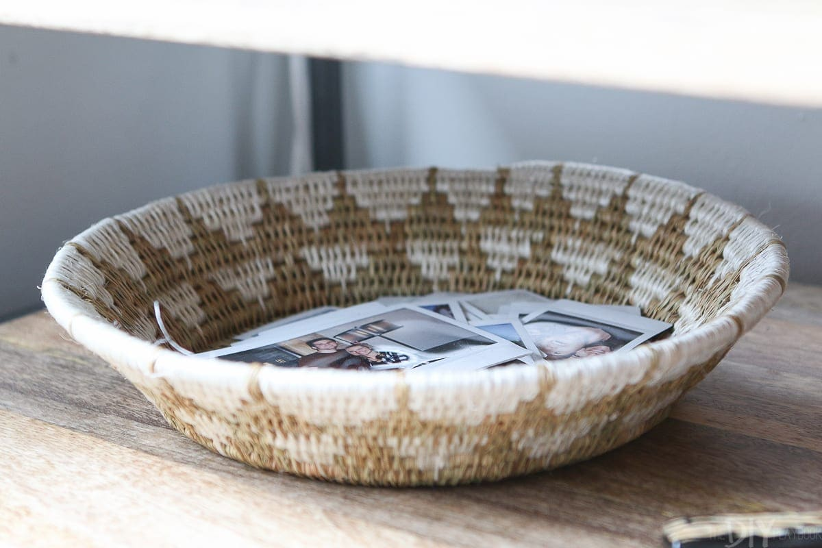 Put polaroid pictures in a basket for personal decor