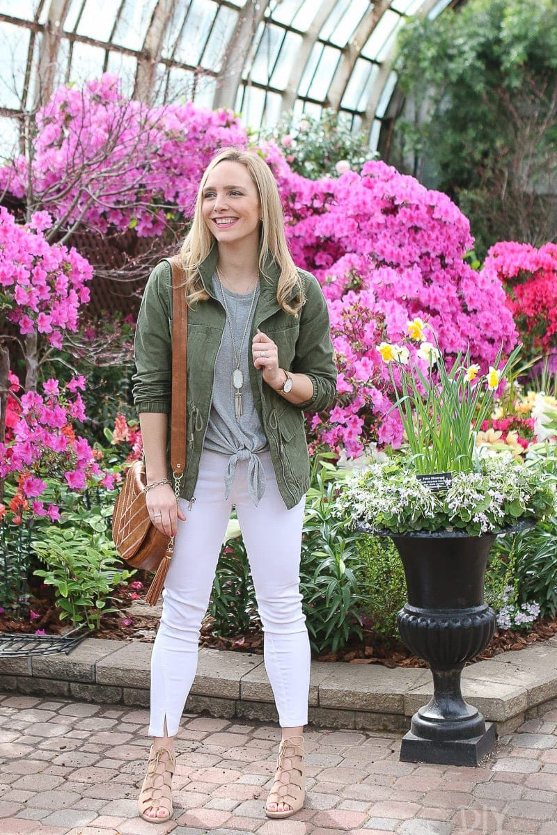 A neutral spring look with white jeans, sandals, and a green jacket.