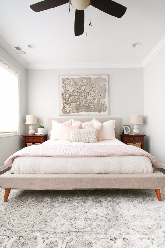 Blush pink accents in a neutral master bedroom