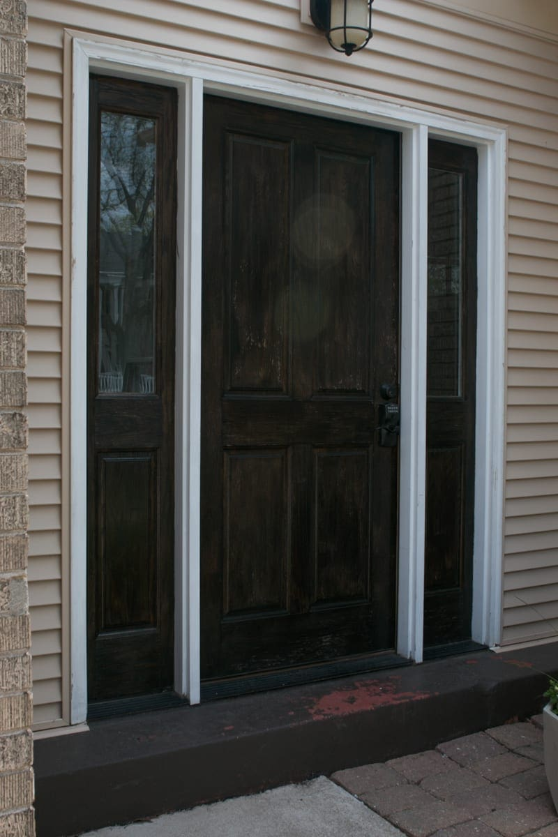 A brown door with chipping paint needs some TLC