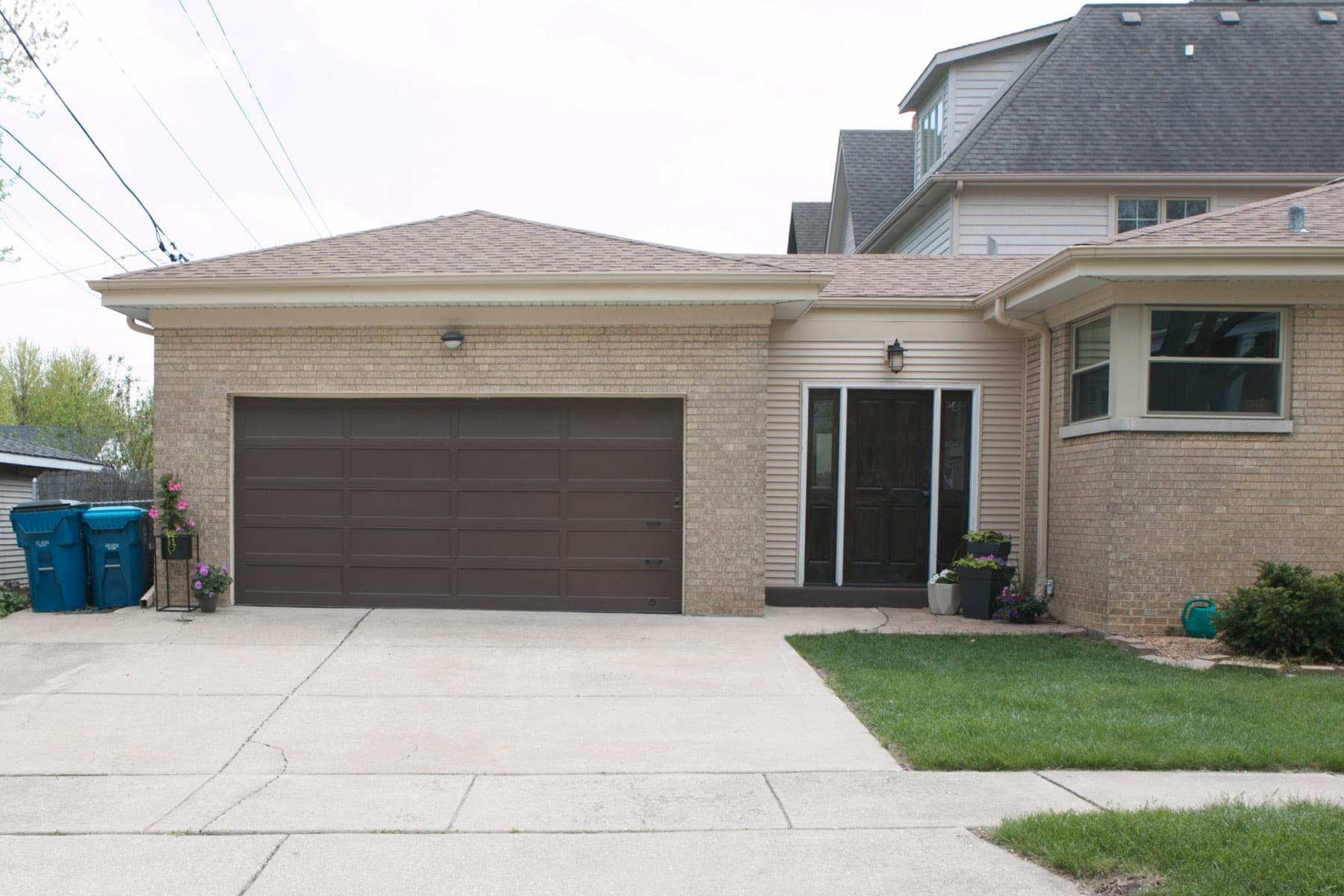A brown garage door needs some attention to improve the curb appeal of this home.