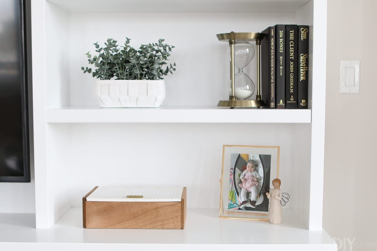 Layer in books, greenery, and picture frames to create the perfect shelfie.