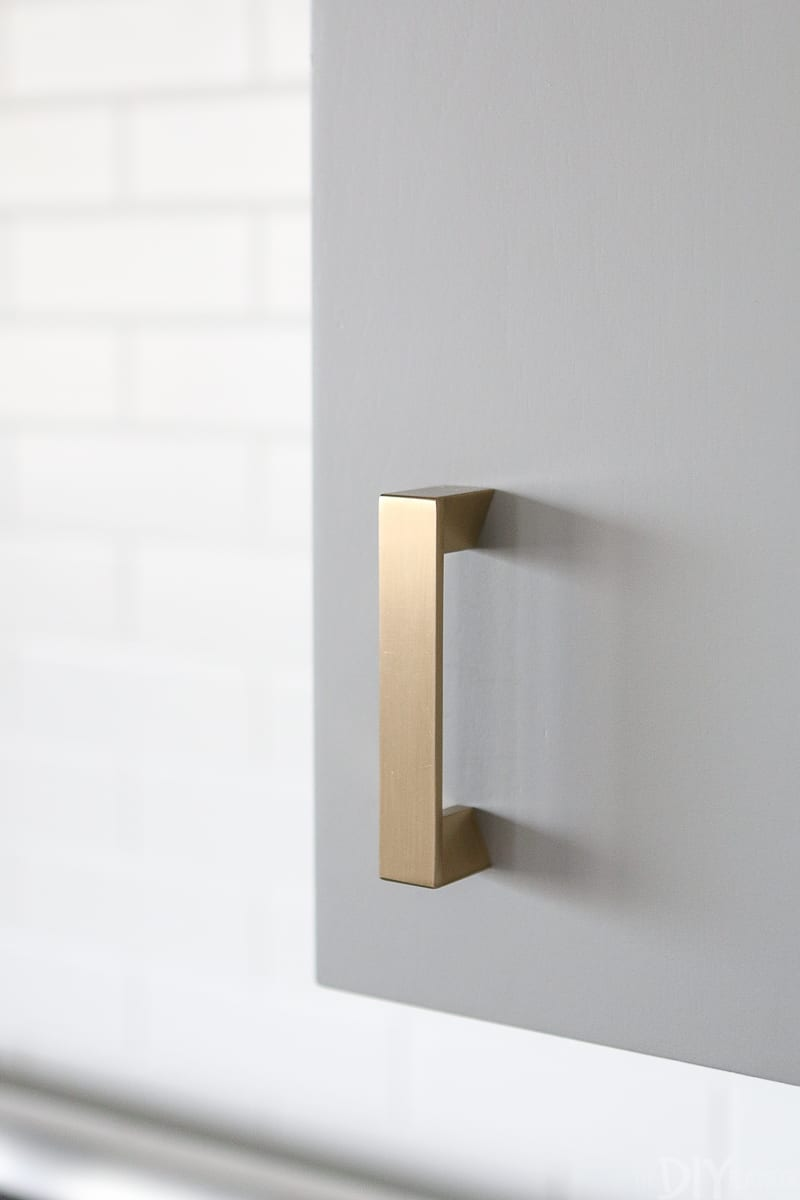 Gold hardware on a gray kitchen cabinet
