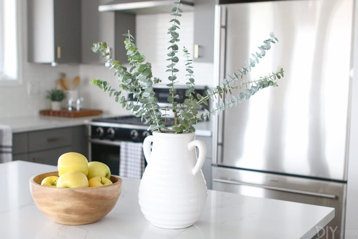 Add eucalyptus to a white vase for kitchen decor.
