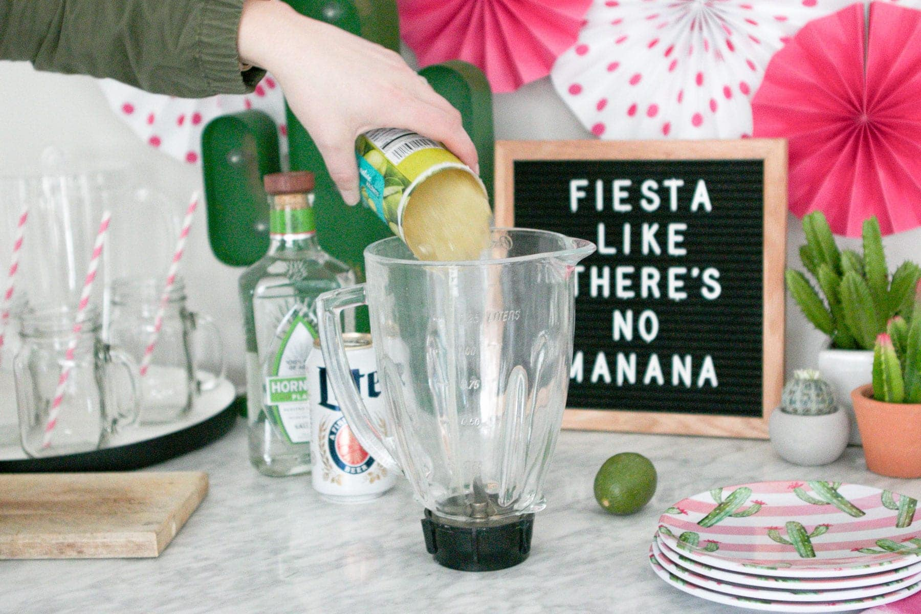pouring limeade into a margarita
