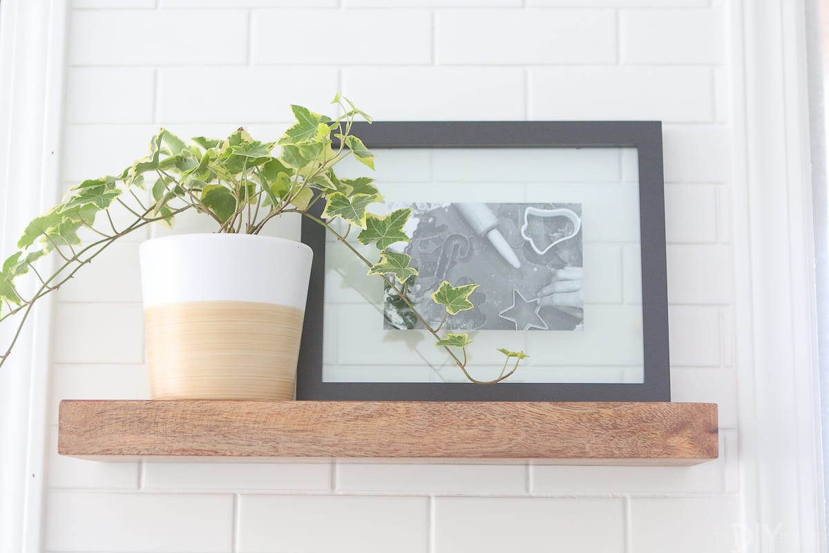 Use frames and plants to accessorize open shelving in the kitchen.