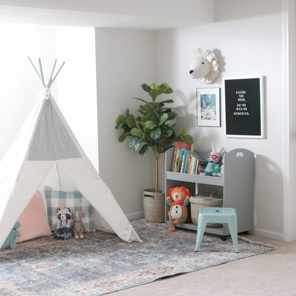 Using a teepee and bookshelves to create an organized playroom.