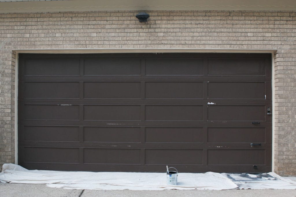 the process of painting our old garage door black