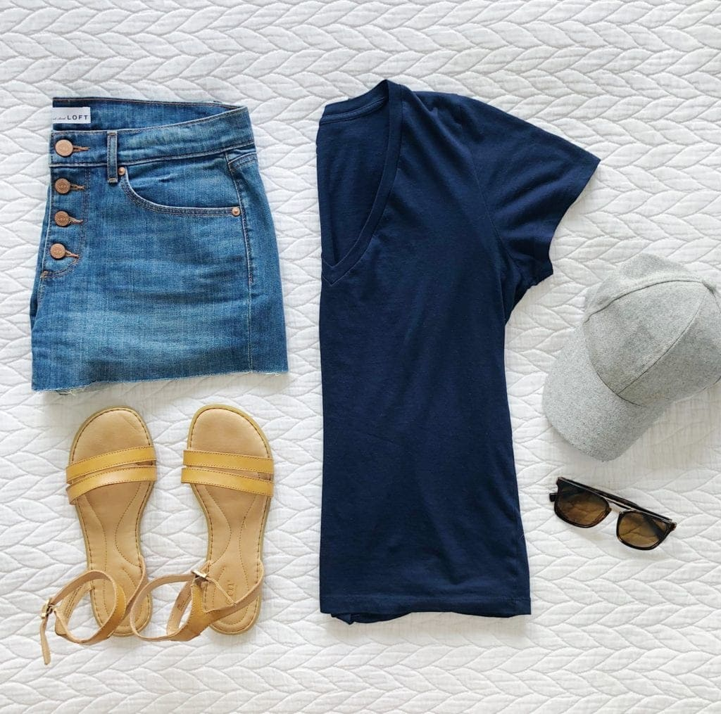 A classic summer look with a navy t-shirt, jean shorts, and sandals